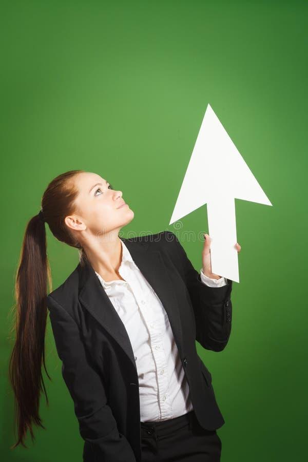 Geschäftsfrau, die Papierpfeil auf grünem Hintergrund hält lizenzfreies stockbild