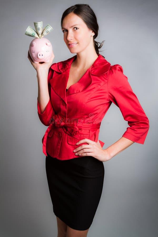 Geschäftsfrau, die Piggy Querneigung anhält lizenzfreies stockfoto
