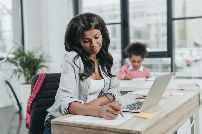Geschäftsfrau, die an Projekt arbeitet, während die Tochter, die Hausarbeit tun, die Arbeit und das Leben Konzept balancieren lizenzfreie stockbilder