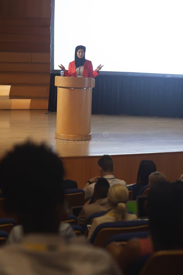 Geschäftsfrau, die Rede vor Publikum im Auditorium gibt lizenzfreies stockbild