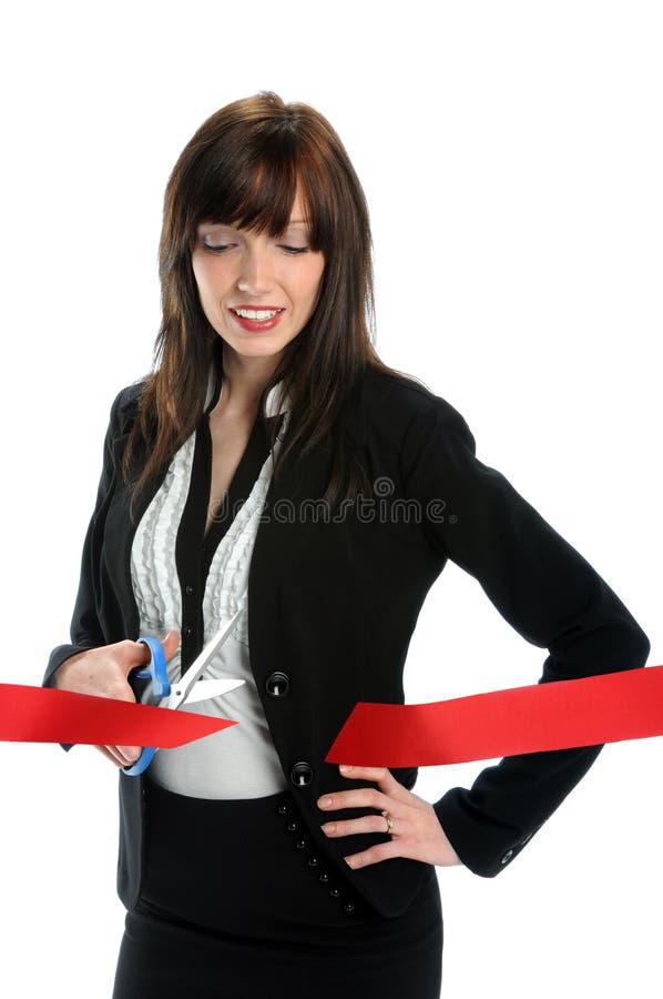 Geschäftsfrau, die rotes Farbband schneidet lizenzfreie stockfotos