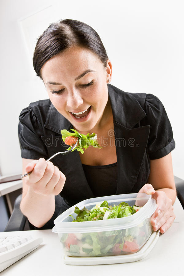 Geschäftsfrau, die Salat am Schreibtisch isst lizenzfreie stockfotos