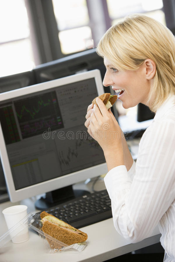 Geschäftsfrau, die Sandwich während der Mittagspause genießt lizenzfreies stockfoto