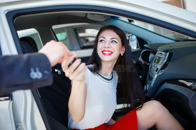 Geschäftsfrau, die Schlüssel ihres Neuwagens vom Händler empfängt lizenzfreie stockfotos