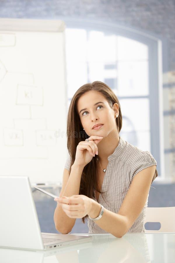 Geschäftsfrau, die am Schreibtisch denkt lizenzfreie stockbilder