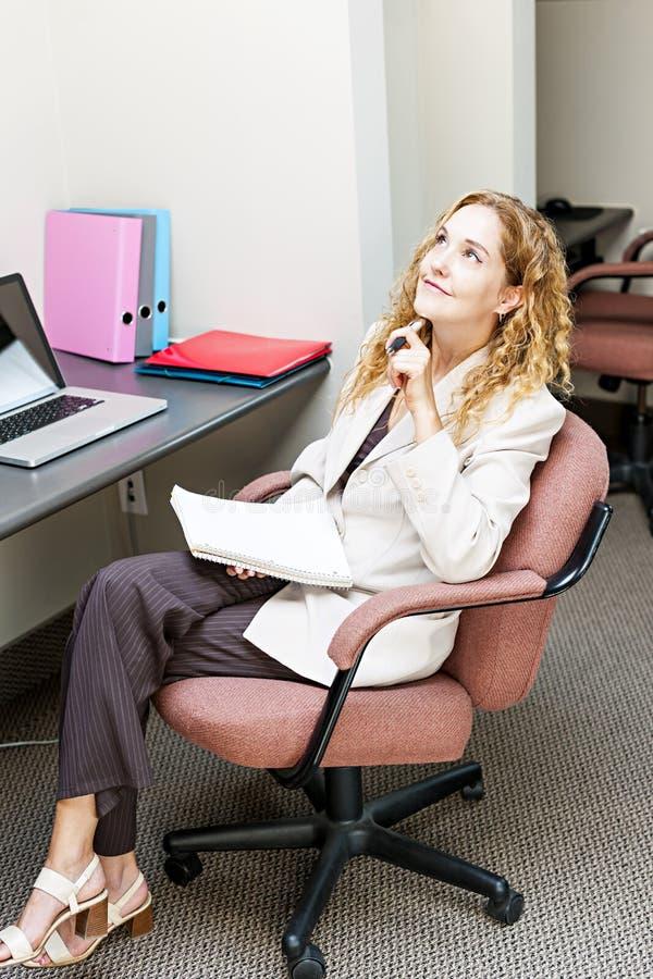 Geschäftsfrau, die am Schreibtisch denkt stockfotografie