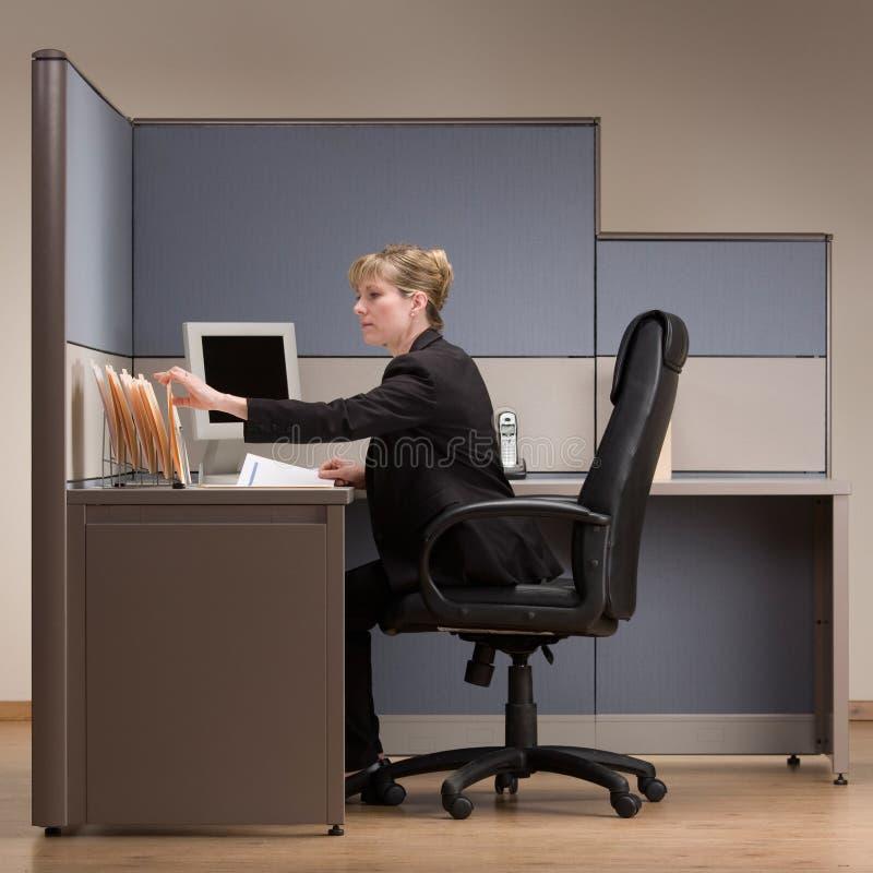 Geschäftsfrau, die am Schreibtisch in der Zelle sitzt stockfotos