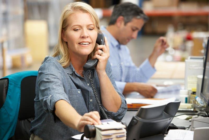 Geschäftsfrau, die am Schreibtisch im Lager arbeitet lizenzfreies stockfoto