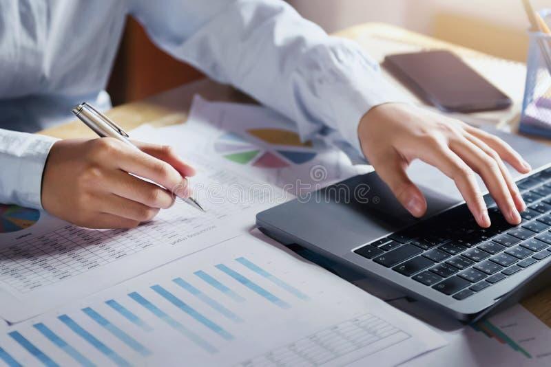 Geschäftsfrau, die an Schreibtisch unter Verwendung des Laptops für Kontrolldaten der Finanzierung arbeitet lizenzfreies stockbild
