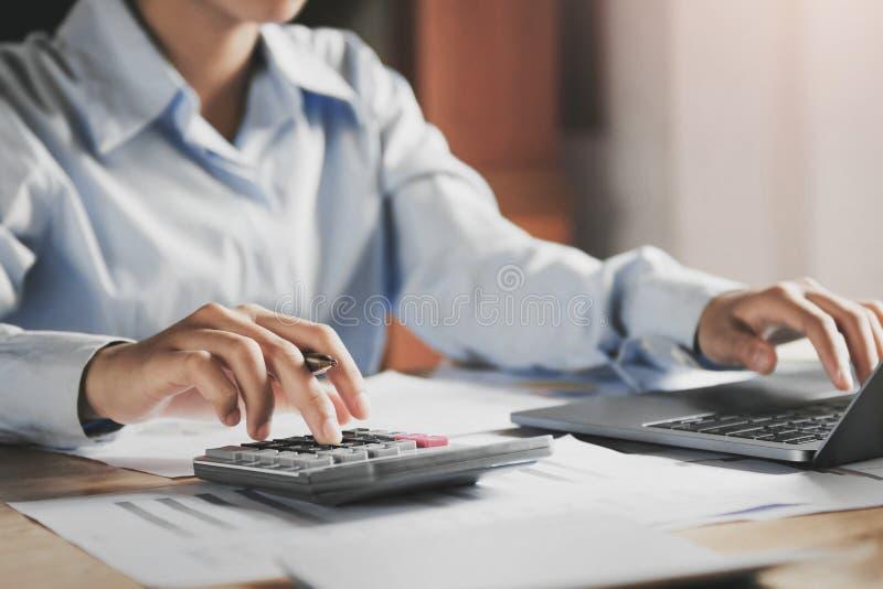 Geschäftsfrau, die an Schreibtisch unter Verwendung des Laptops für Kontrolldaten der Finanzierung arbeitet lizenzfreie stockfotografie
