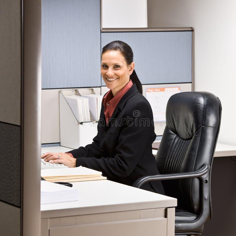 Geschäftsfrau, die am Schreibtischlächeln sitzt stockfoto