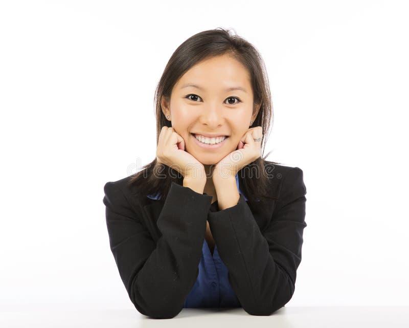 Geschäftsfrau, die am Schreibtischlächeln sitzt stockfotografie