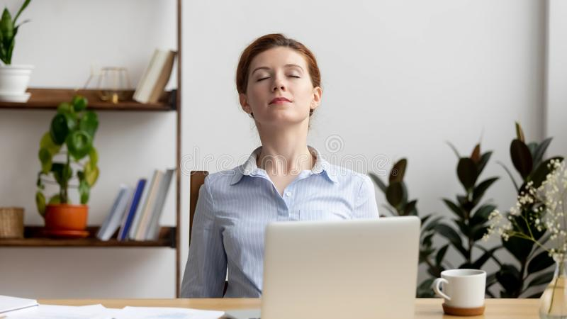 Gesch?ftsfrau, die Schultern nach glaubendem Unbehagen der harten Arbeit bei der Arbeit ausdehnt stockfotografie
