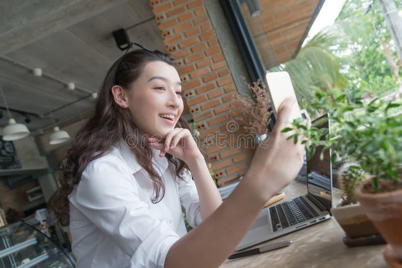 Geschäftsfrau, die selfie am intelligenten Telefon in der Kaffeeabschaltzeit an ihrem Arbeitsplatz nimmt vermarktendes on-line-Ko stockbilder