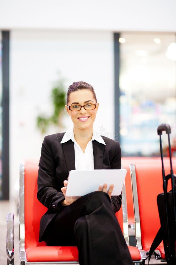 Geschäftsfrau, die Tablette am Flughafen verwendet stockbild