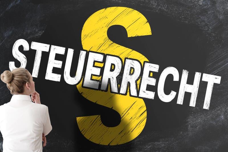Geschäftsfrau, die Tafel mit dem Wort STEUERRECHT, deutsch nach Steuerrecht oder Steuerrecht, und Paragraphzeichen betrachtet stockbilder