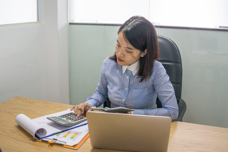 Geschäftsfrau, die Taschenrechner verwendet, um Finanzbericht zu analysieren stockbilder