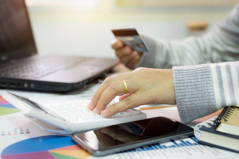 Geschäftsfrau, die Taschenrechner verwendet und Kreditkarte hält lizenzfreie stockfotos