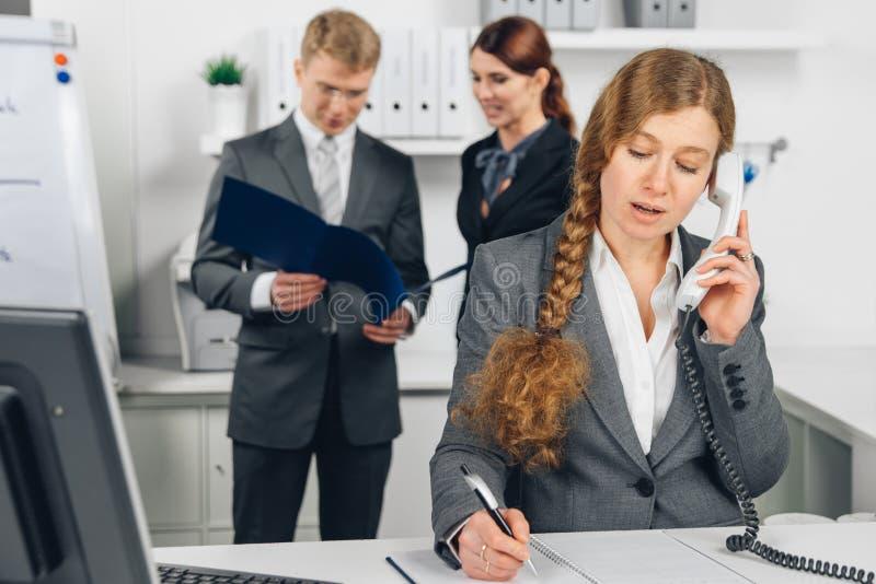 Geschäftsfrau, die am Telefon im Büro spricht lizenzfreie stockfotos