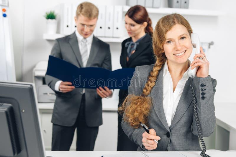 Geschäftsfrau, die am Telefon im Büro spricht lizenzfreie stockbilder