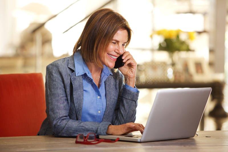Geschäftsfrau, die am Telefon spricht und Laptop-Computer betrachtet lizenzfreie stockfotografie