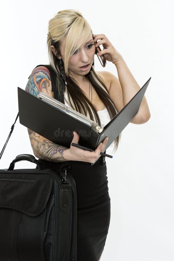 Geschäftsfrau, die telefonisch spricht und Anmerkung schaut stockfoto