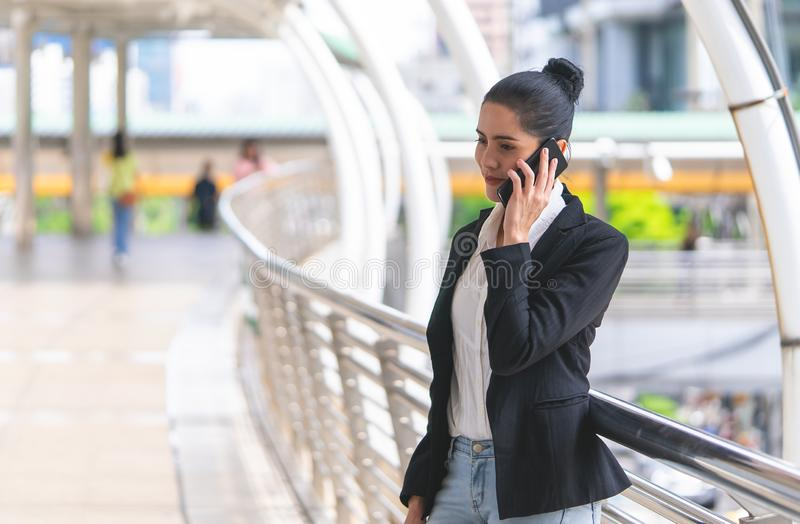 Geschäftsfrau, die um Mobile auf Wegweise ersucht lizenzfreie stockbilder