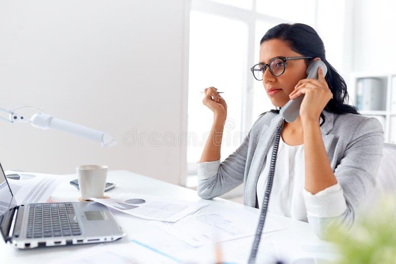 Geschäftsfrau, die um Schreibtischtelefon im Büro ersucht lizenzfreies stockfoto