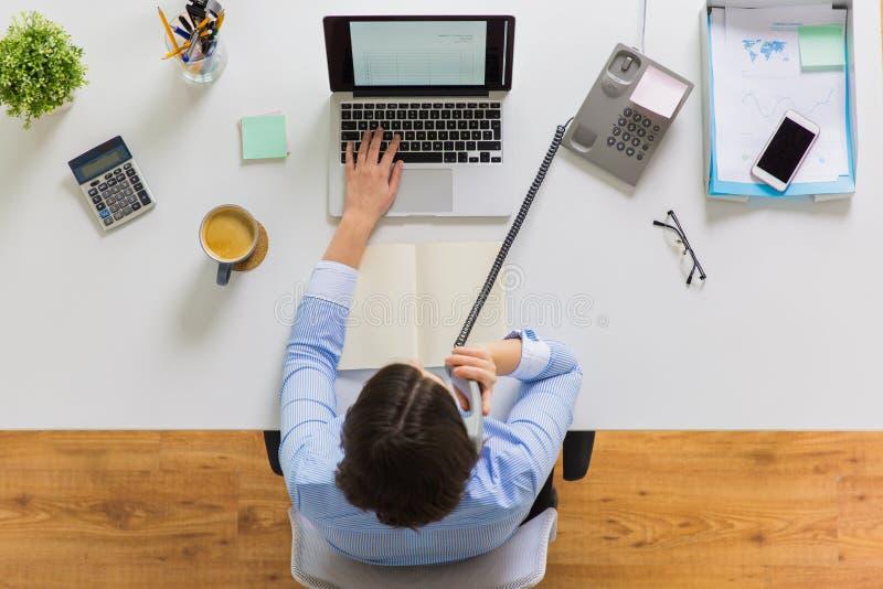 Geschäftsfrau, die um Telefon am Bürotisch ersucht stockfotografie