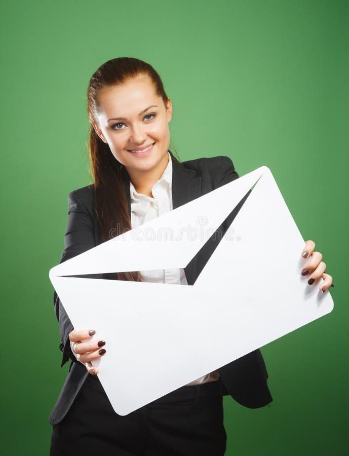 Geschäftsfrau, die Umschlag auf grünem Hintergrund hält lizenzfreies stockbild
