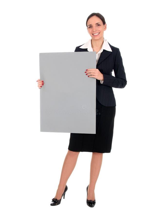 Geschäftsfrau, die unbelegtes Plakat anhält lizenzfreie stockfotografie