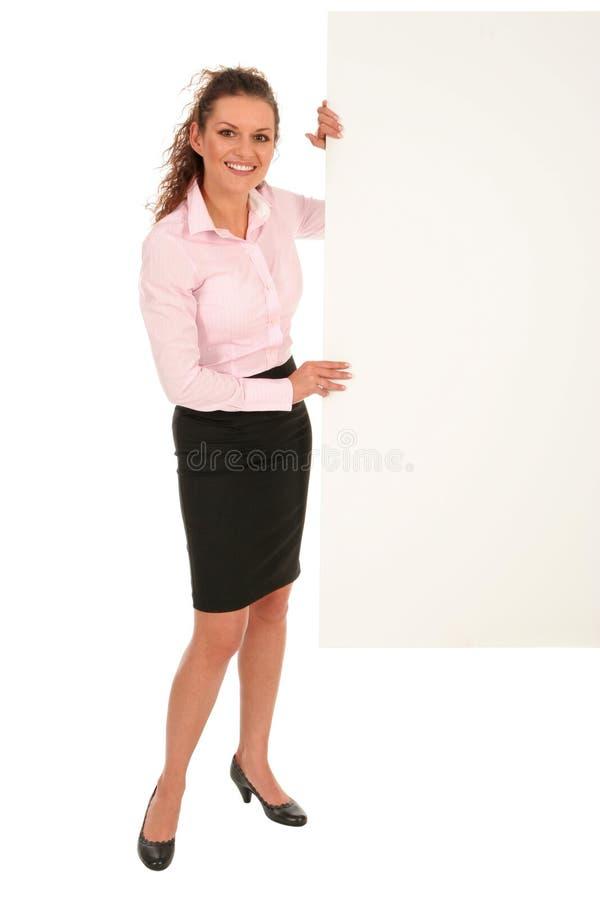 Geschäftsfrau, die unbelegtes Plakat anhält lizenzfreies stockbild