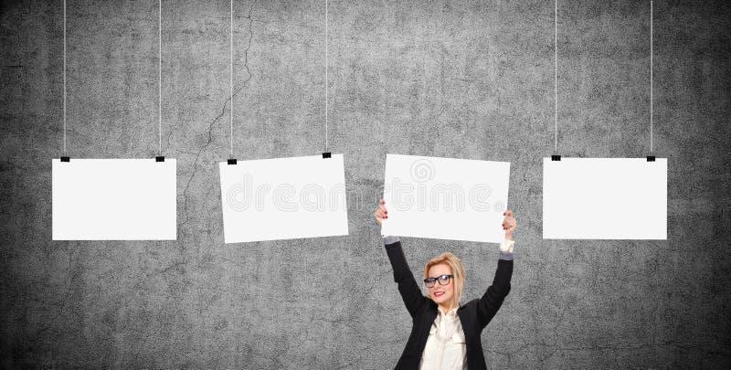 Geschäftsfrau, die unbelegtes Plakat anhält stockbild