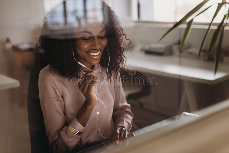 Geschäftsfrau, die unter Verwendung der Kopfhörer beim zu Hause arbeiten spricht lizenzfreie stockbilder