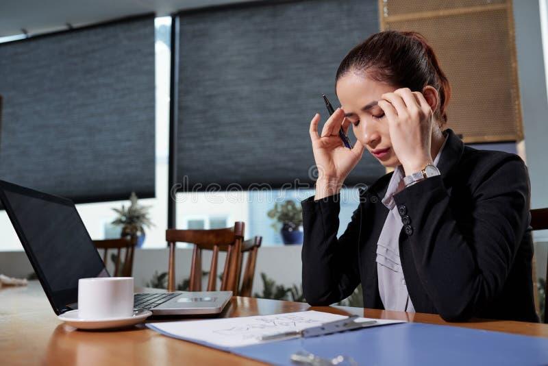Gesch?ftsfrau, die versucht, sich auf Arbeit zu konzentrieren lizenzfreie stockfotos