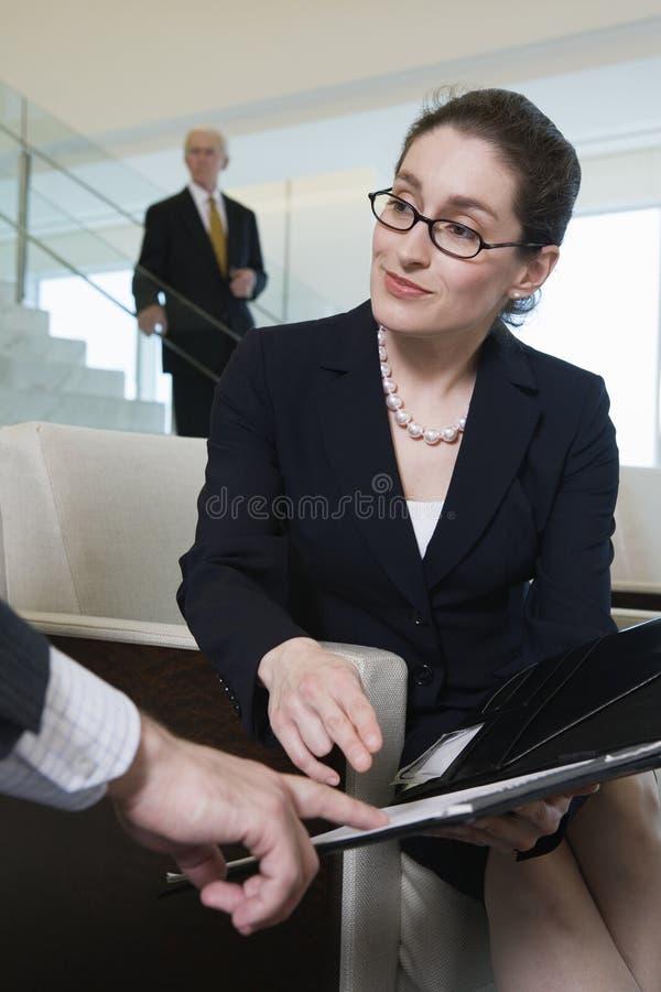 Geschäftsfrau, die Verträge in der modernen Vorhalle wiederholt. lizenzfreie stockbilder