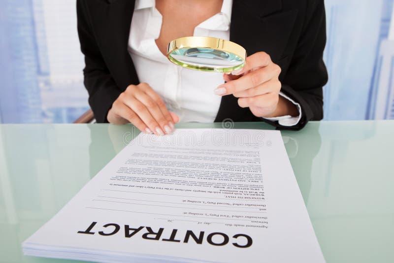 Geschäftsfrau, die Vertrag mit Lupe nachforscht stockbilder