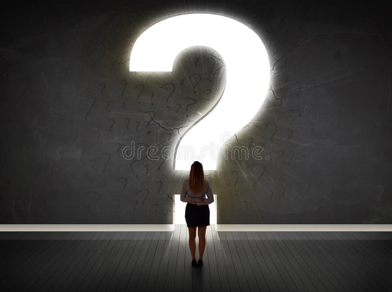 Geschäftsfrau, die Wand mit einem hellen Fragezeichen betrachtet lizenzfreies stockfoto