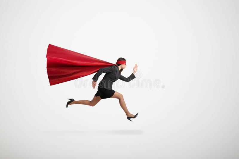 Geschäftsfrau, die wie schneller Betrieb des Superhelden sehr trägt stockfoto