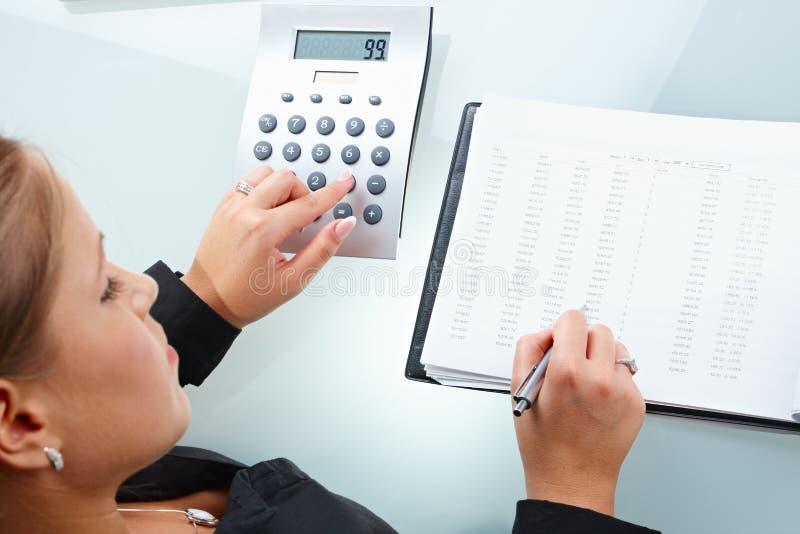 Geschäftsfrau, die Zahlen zusammenzählt stockbilder