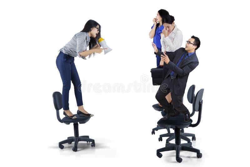 Geschäftsfrau, die zu ihrer Teamwork schreit stockfotos