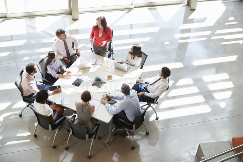 Geschäftsfrau, die zu Teambesprechung, erhöhter Ansicht spricht stockbild