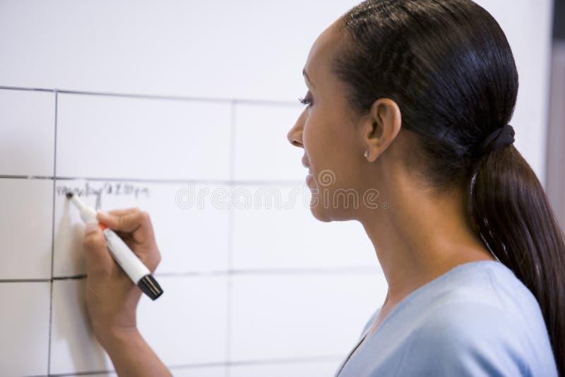 Geschäftsfrau, die zuhause auf löschbaren Vorstand schreibt stockfoto
