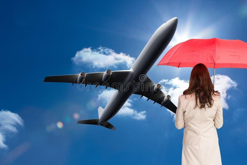 Geschäftsfrau, die zurück zu der Kamera hält roten Regenschirm steht lizenzfreie stockfotografie
