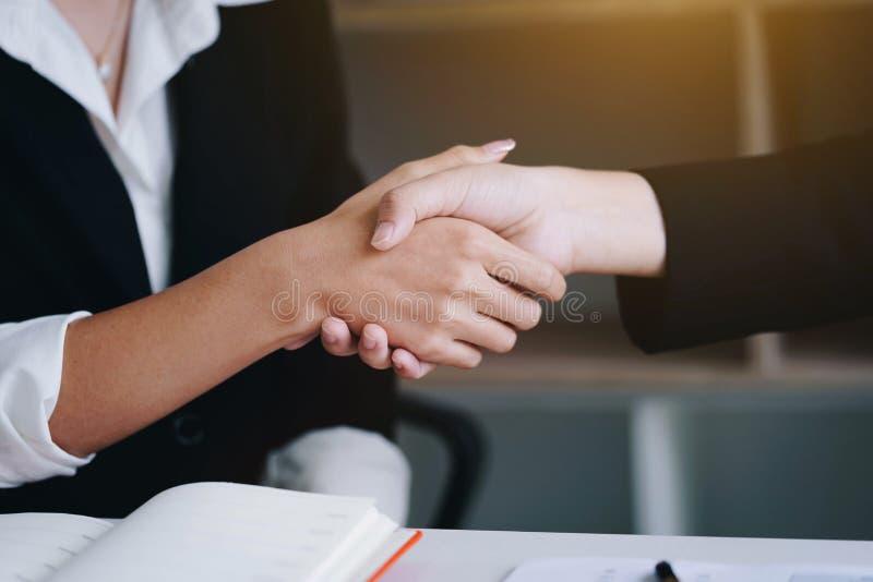 Geschäftsfrau, die zusammen Hand für eine komplette Geschäftsvereinbarung rüttelt stockfotografie