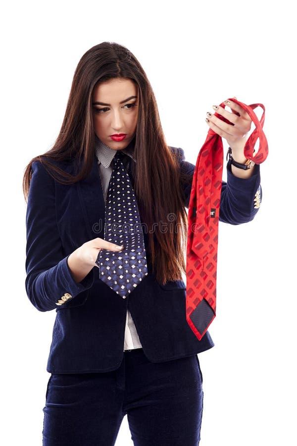 Geschäftsfrau, die zwischen blauer und roter Krawatte wählt lizenzfreie stockbilder