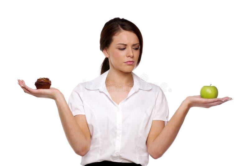 Geschäftsfrau, die zwischen Kuchen und Frucht wählt lizenzfreies stockbild