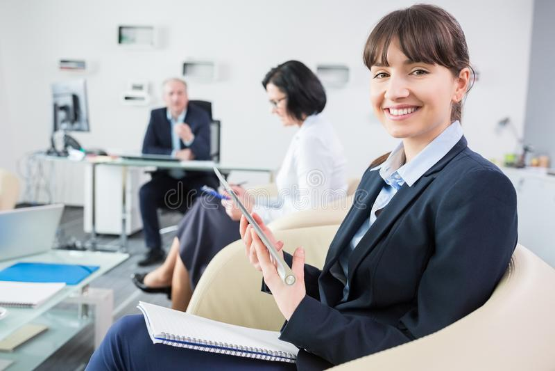Geschäftsfrau With Digital Tablet, das auf Stuhl im Büro sitzt stockbild