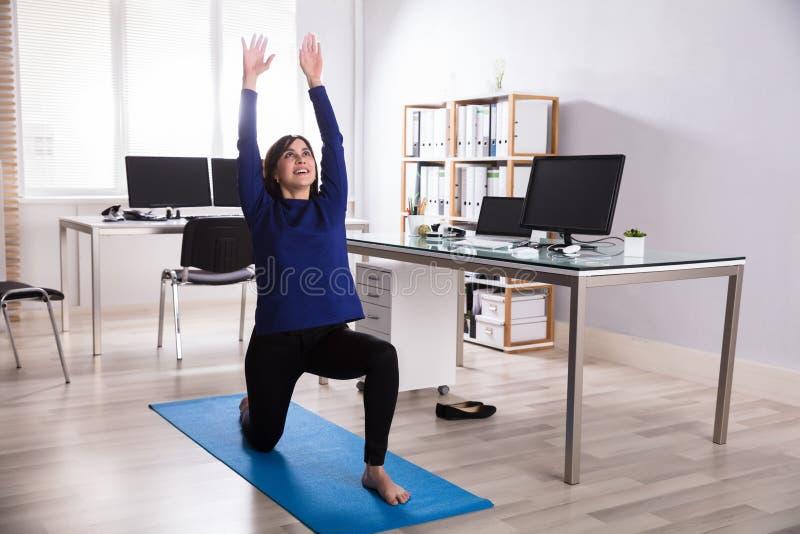 Geschäftsfrau-Doing Workout In-Büro lizenzfreie stockbilder