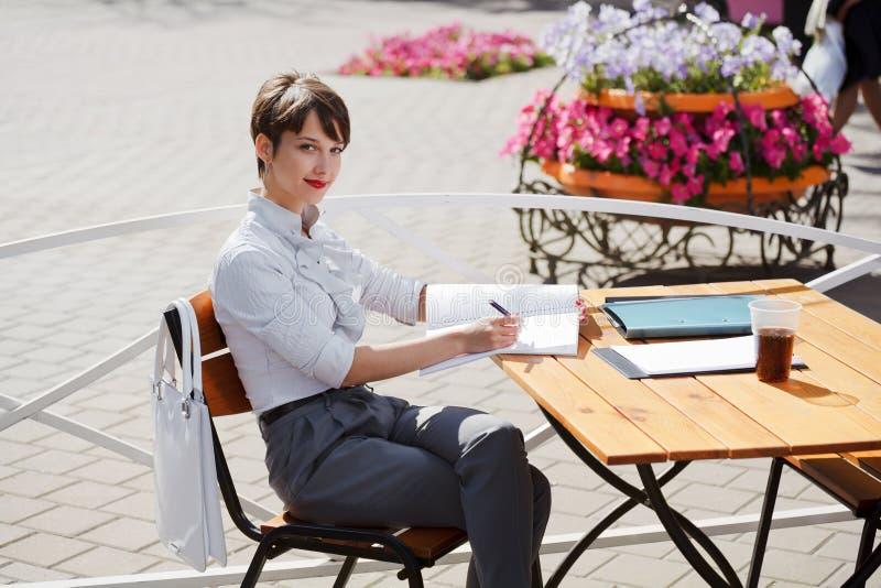 Geschäftsfrau an einem Bürgersteigkaffee stockfoto